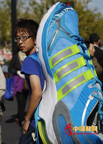 青年为阿迪达斯鞋服运动品牌宣传,身背硕大运动鞋观战